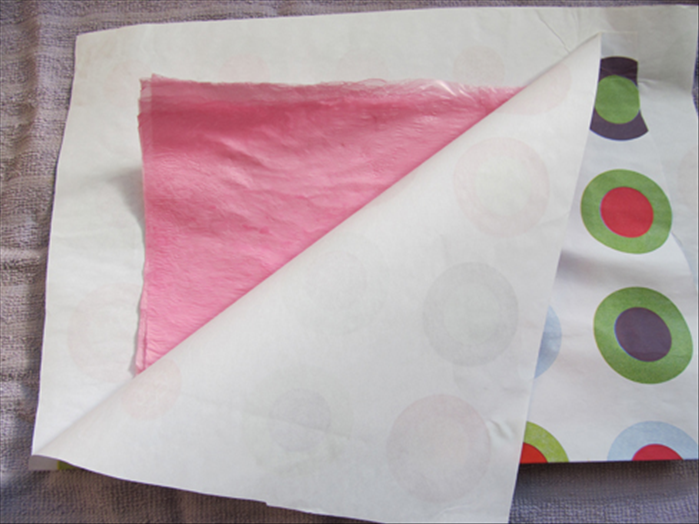 Lift the paper to see if the layers have fused together. If they haven't fused, cover the bag again and go over it a few more times.  Flip the paper covered bag over to the back side and go over it some more. Check to see the results and repeat if necessary