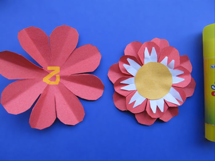Put glue on the center of the next smallest petal layer and place the layered flower on top with the petals in between