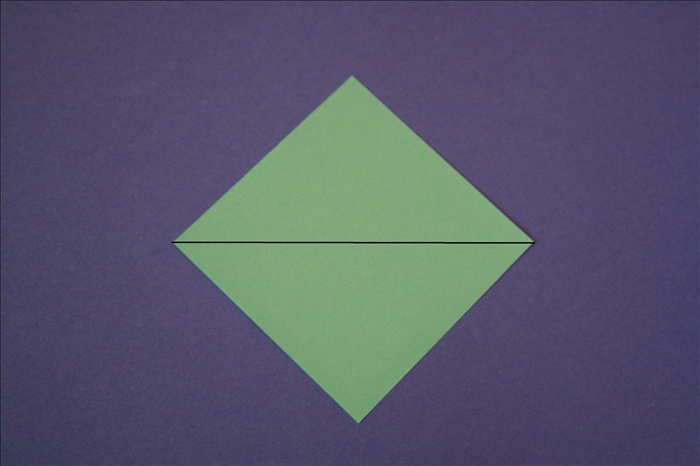 Place the paper so that the points are at the top, bottom and sides.  Bring the top point down to the bottom point to fold it in half.
