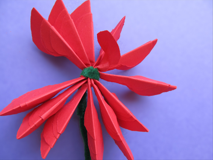 Bring the petals up and around the wound wire to make a circle  Lift one of the smallest petals and fold it back in the opposite direction