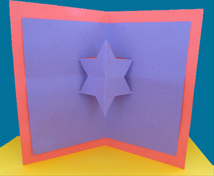 <p> Open to see your ready card. Now you can write your greeting and decorate it.</p>  <p> If you want to glue a smaller star on top of the cut star, follow  the direction in steps 2 to 6 with a</p>  <p> smaller square.</p>