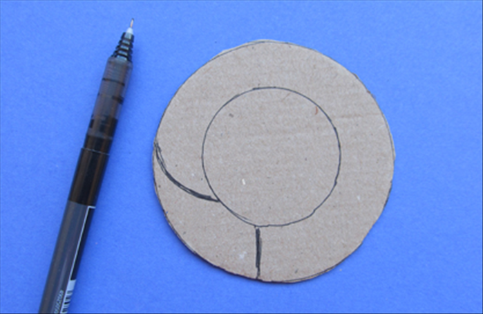 Draw a straight line connecting the 2 circle - a little to the left of the bottom center Draw a curved line upward as shown in the picture. Cut between the lines you drew and the lines of the inner circle