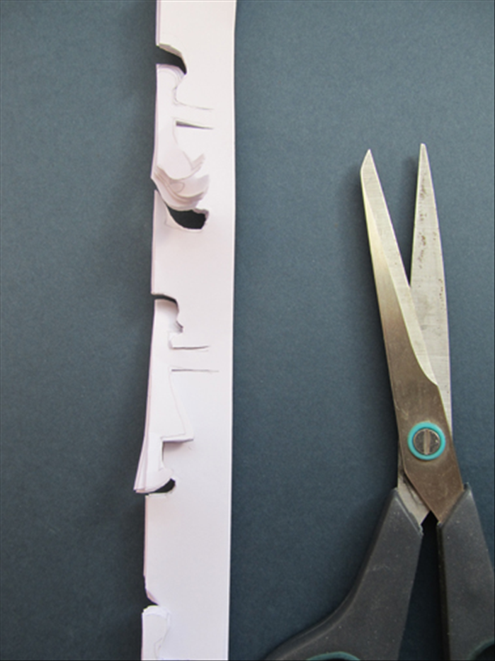Cut along the lines you made. Make sure to stop cutting a little less than ½ inch from the edge of the arm so that the figures remain attached.