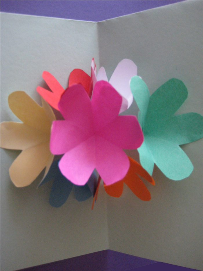 Materials: 7 squares of paper the same size for the flowers Thick paper for the card base scissors paper glue