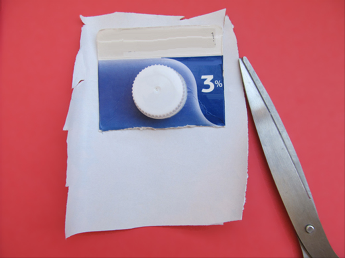 Use the top of the milk carton to measure and cut a piece of decorative paper as shown in the picture