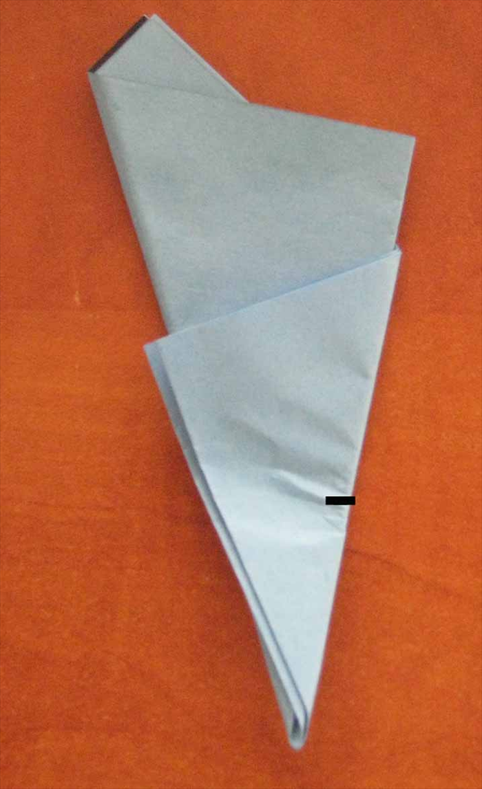 Turn paper so that the narrow point is on the bottom.    Take the bottom point and fold it up half way of the right side of the outer  triangle and pinch for  a reference point to start cutting