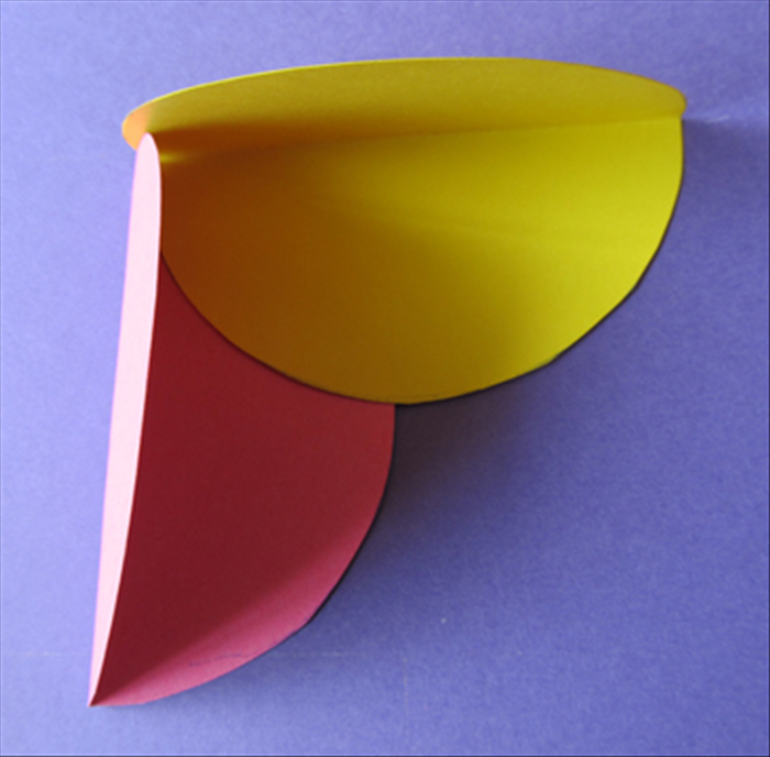 Place one color circle so that the straight folded edge makes a corner with a different color.