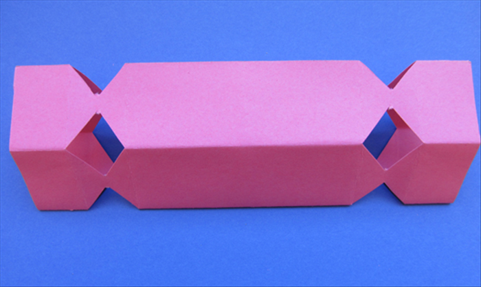 Stick your fingers inside and push outwards to make the box shape