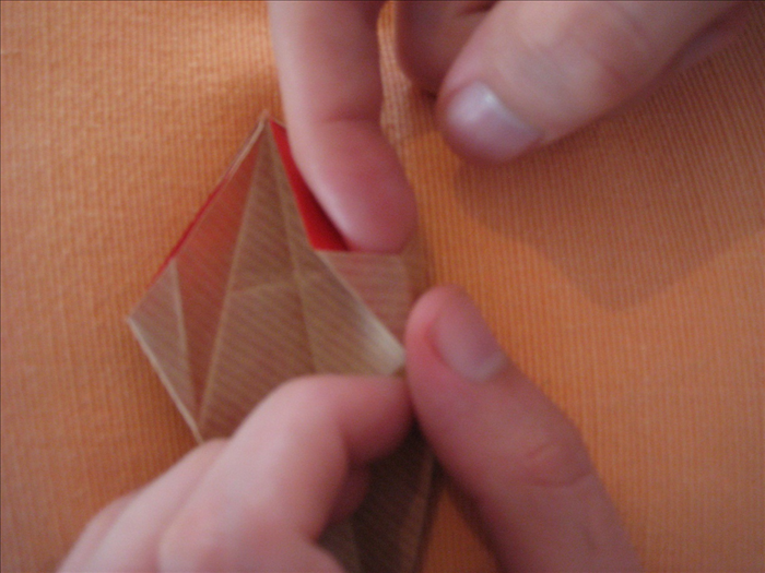 Unfold the last 2 steps On each side separately, stick your finger between the  2 layers from the top and squash down with your thumb along the crease coming up
