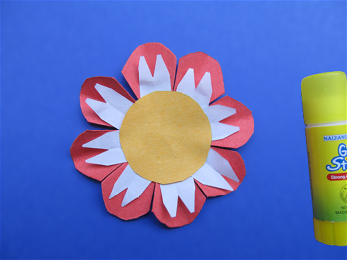 Put a little glue on the center of the yellow circle. Place the circle in the center of the smallest petal layer and stick the white papers under it. The creases of the petal and the white paper should be aligned.