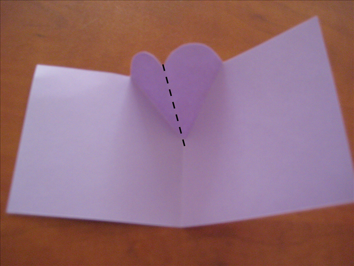 Unfold the card . Push the heart forward from the back and pinch the center fold on the inside Press the V fold from the outside to flatten it.