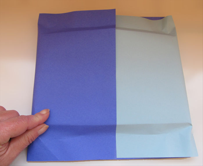 Flip the present over to the back side. Pinch the paper along the top and bottom edges of the present.