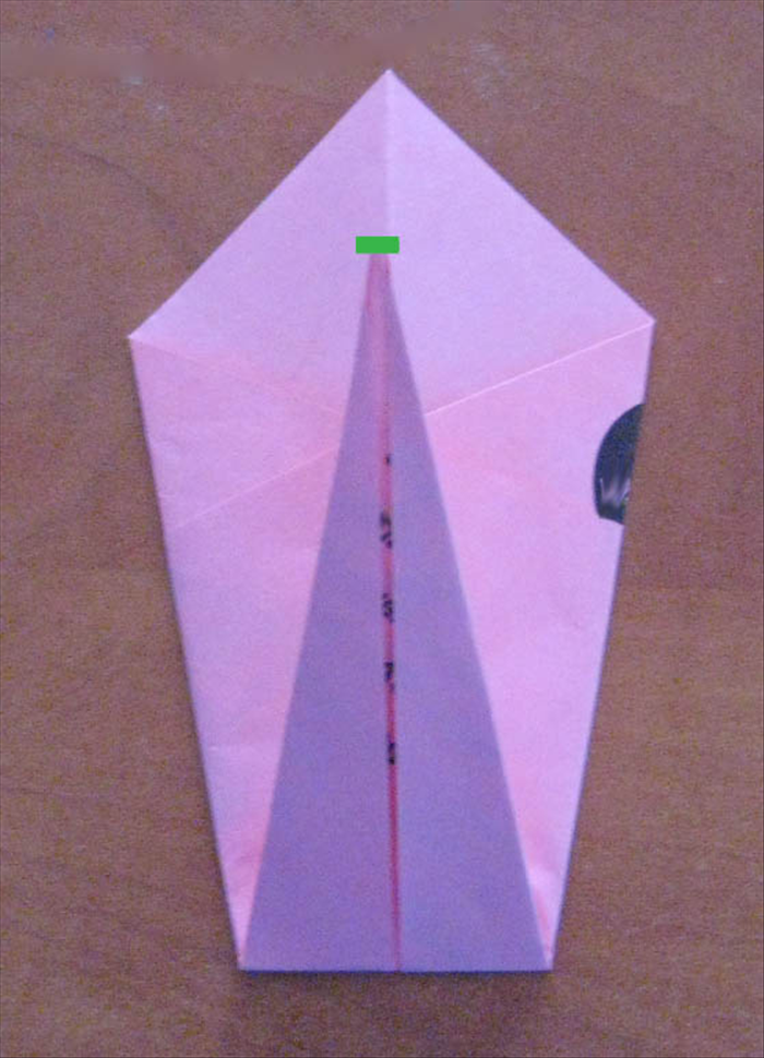 Fold the bottom point up  towards the top , halfway up the top triangle.