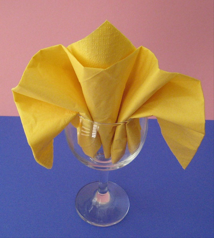 Pull down the sides and your Fleur de lys napkin fold is finished.