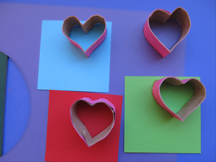 Put glue along one edge of the heart and press it down on the colored paper you want the front of the heart to be.