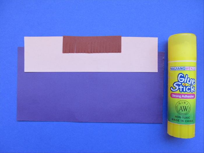 Align the paper for the bangs to the top and center of the skin colored paper and glue in place